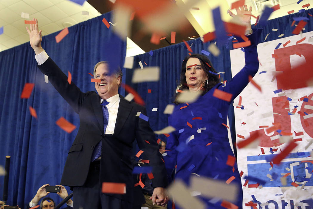 Democratic candidate for U.S. Senate Doug Jones and his wife Louise wave to supporters before speaking during an election-night watch party Tuesday, Dec. 12, 2017, in Birmingham, Ala. In a stunnin ...