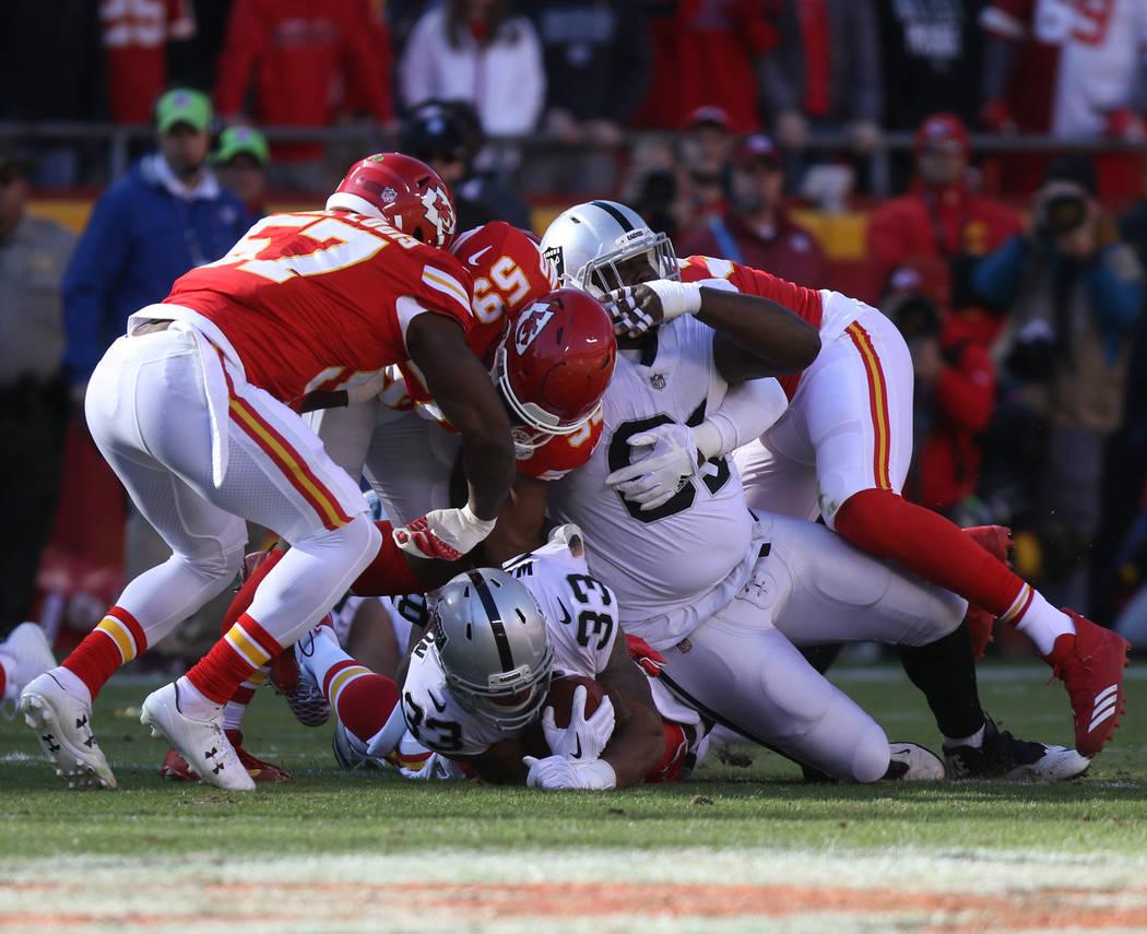 Oakland Raiders running back DeAndre Washington (33) is tackled Kansas City Chiefs inside linebacker Reggie Ragland (59) during the first half of a NFL game in Kansas City, Mo., Sunday, Dec. 10, 2 ...