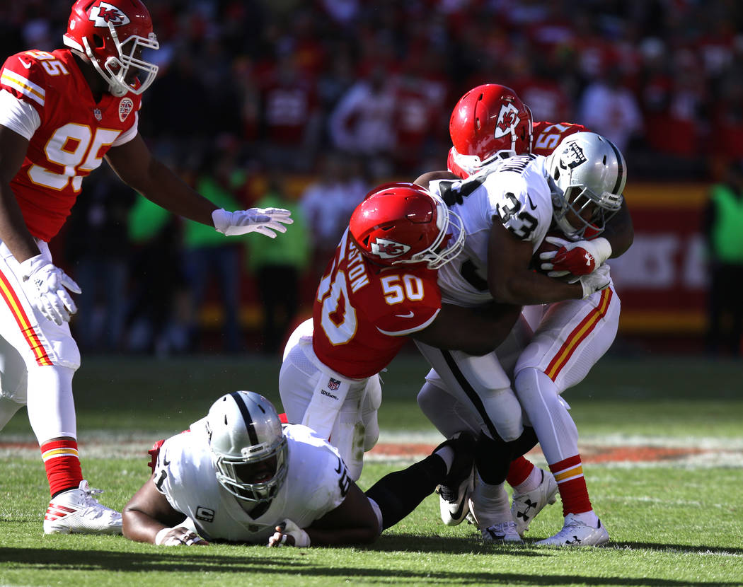 Oakland Raiders running back DeAndre Washington (33) is tackled by Kansas City Chiefs linebacker Kevin Pierre-Louis (57) and outside linebacker Justin Houston (50) during the first half of a NFL g ...