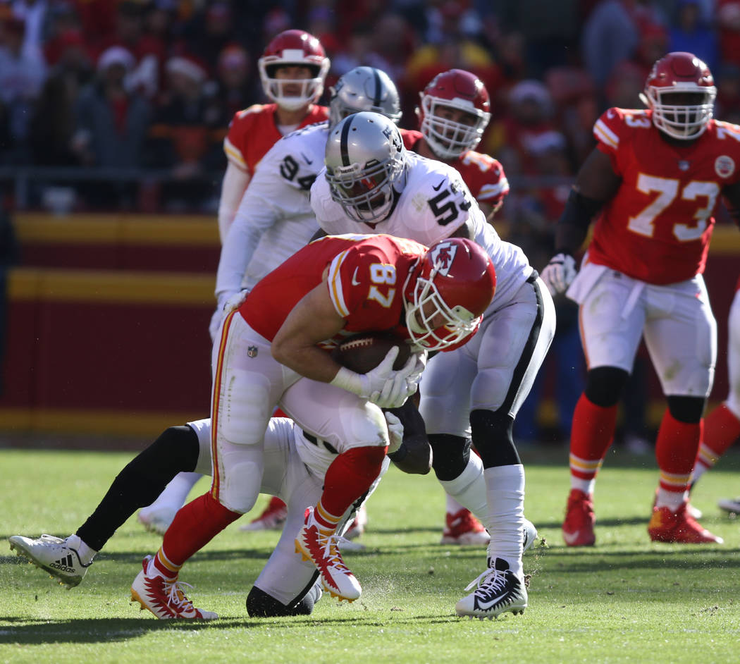 Kansas City Chiefs tight end Travis Kelce (87) catches a pass as Oakland Raiders middle linebacker NaVorro Bowman (53) tries to tackle him during the first half of a NFL game in Kansas City, Mo.,  ...
