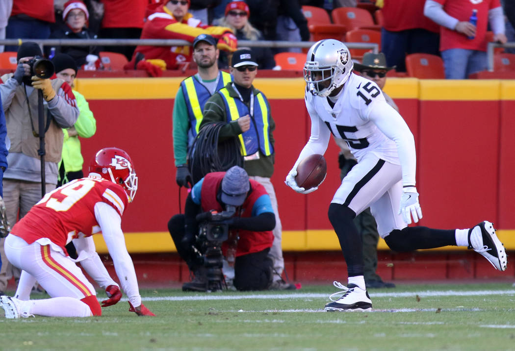 Oakland Raiders wide receiver Michael Crabtree (15) catches a pass as Kansas City Chiefs cornerback Terrance Mitchell (39) looks to tackle him during the first half of a NFL game in Kansas City, M ...
