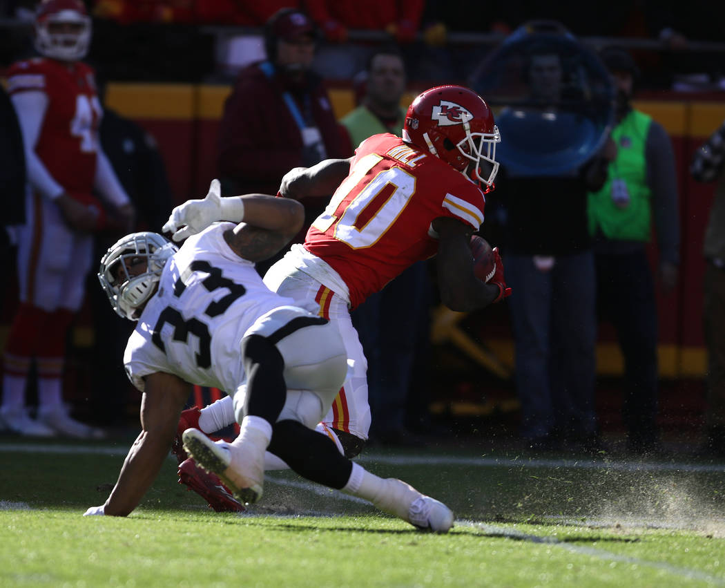 Kansas City Chiefs wide receiver Tyreek Hill (10) breaks loose from Oakland Raiders running back DeAndre Washington's  (33) tackle attempt during the first half of a NFL game in Kansas City, Mo.,  ...