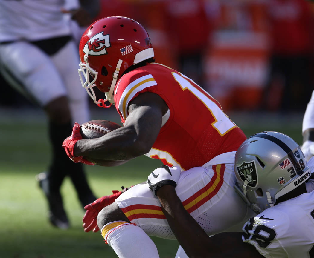 Kansas City Chiefs wide receiver Tyreek Hill (10) is brought down by Oakland Raiders cornerback T.J. Carrie (38) during the first half of a NFL game in Kansas City, Mo., Sunday, Dec. 10, 2017. Hei ...