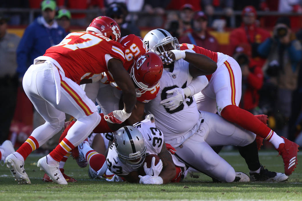 Oakland Raiders running back DeAndre Washington (33) is tackled Kansas City Chiefs inside linebacker Reggie Ragland (59) during the first half of a NFL game in Kansas City, Mo., Sunday, Dec. 10, 2 ...