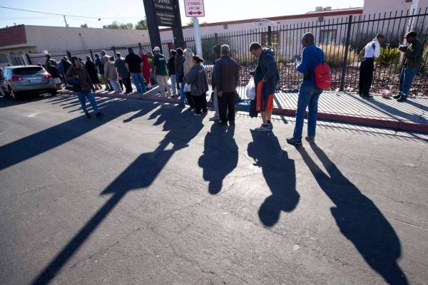 A line homeless people wait for food handouts on Foremaster Lane between Las Vegas Blvd. and Ma ...