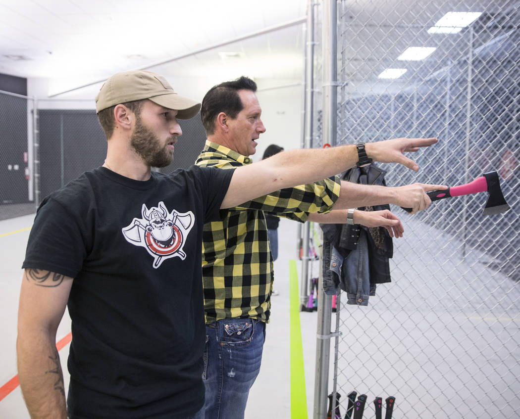 "Co-owner Anthony Cools, right, takes instruction from Keith Waggoner at Axe Monkeys Vegas on Wednesday, Feb. 1, 2017, in Las Vegas. ""I can see this being highly addictive,"" said  ..."