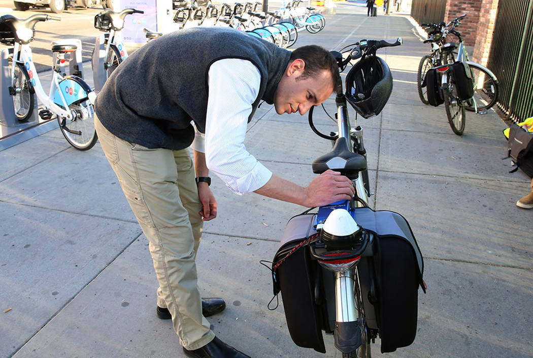 Alessandron Negri, software engineer at Charles River Analytics, demonstrates bicycling safety technology at the corner of Seventh Street and Carson Street Wednesday, Dec. 13, 2017, in Las Vegas.  ...