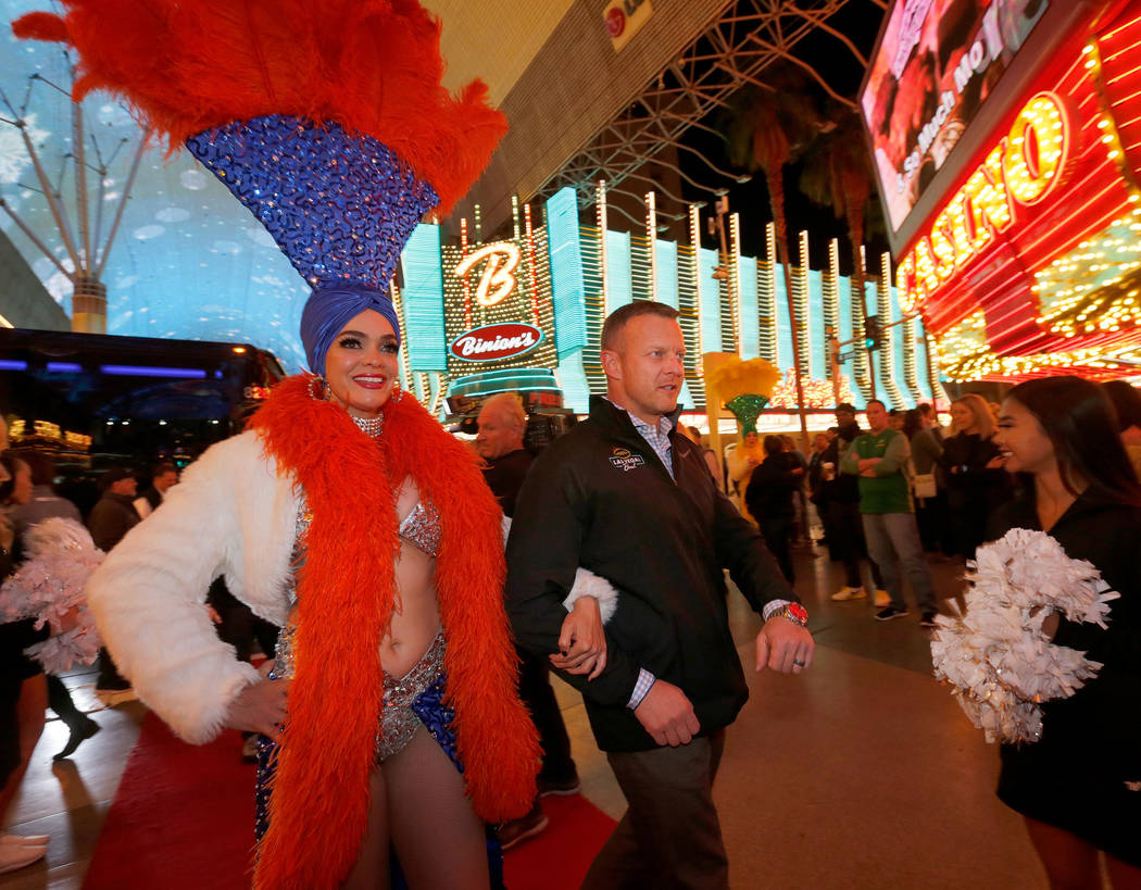 A showgirl escorts Boise State Broncos head coach Bryan Harsin to the Las Vegas Bowl welcome reception at Fremont Street Experience in Las Vegas, Wednesday, Dec. 13, 2017, as Harsin and his team a ...