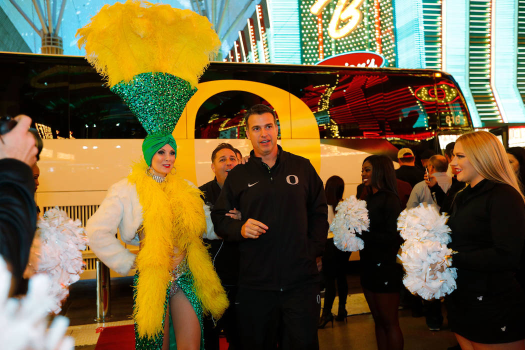 A showgirl escorts Oregon Ducks head coach Mario Cristobal to the Las Vegas Bowl welcome reception at Fremont Street Experience in Las Vegas, Wednesday, Dec. 13, 2017, as Cristobal and his team ar ...