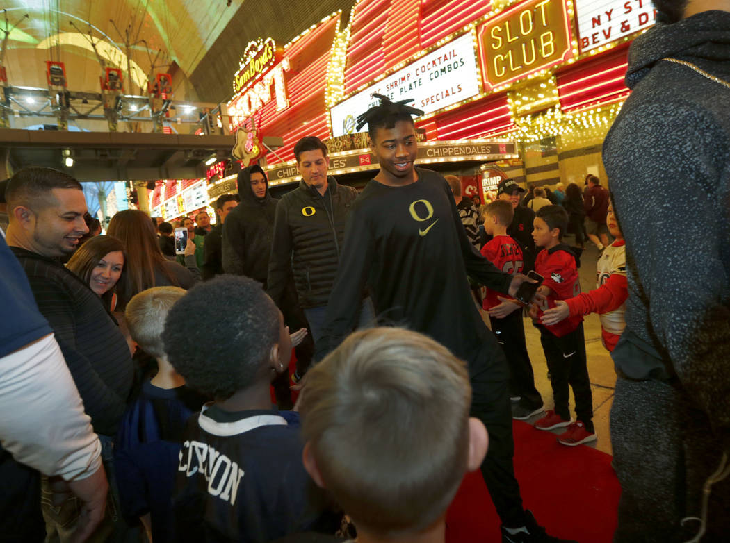 Oregon Ducks players and staff members arrive at the Las Vegas Bowl welcome reception at Fremont Street Experience in Las Vegas, Wednesday, Dec. 13, 2017.  Oregon Ducks and Boise State Broncos mee ...
