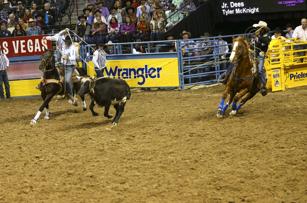 Tyler McKnight, left, and Jr. Dees take part in the team roping competition in the sixth go-round of the Wrangler National Finals Rodeo, Tuesday, Dec. 12, 2017, at the Thomas & Mack Center in  ...