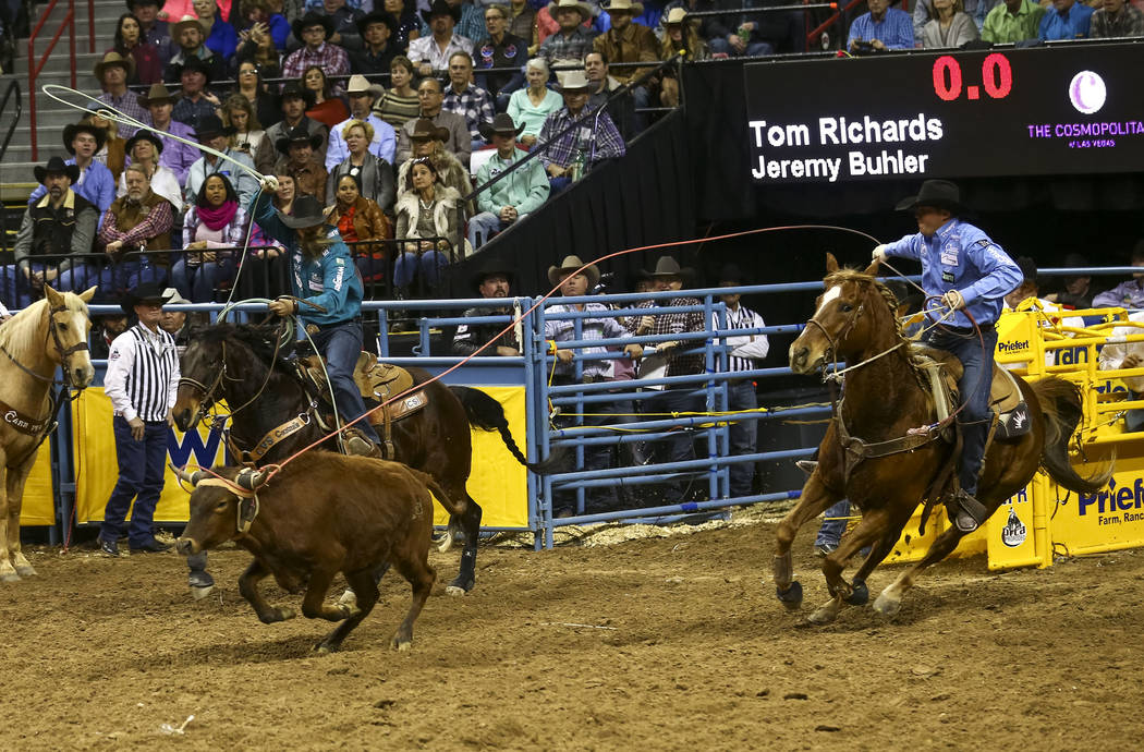 Jeremy Buhler, left, and Tom Richards take part in the team roping competition in the sixth go-round of the Wrangler National Finals Rodeo, Tuesday, Dec. 12, 2017, at the Thomas & Mack Center  ...