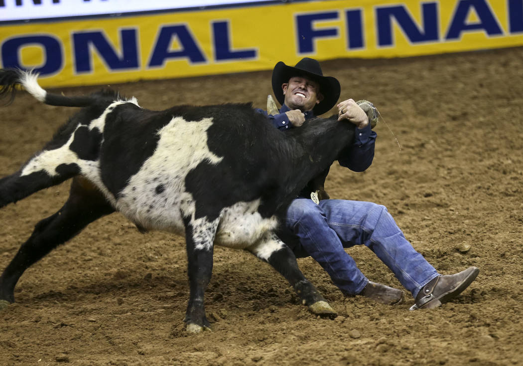 Baylor Roche of Tremonton, Utah takes part in the steer wrestling competition in the sixth go-round of the Wrangler National Finals Rodeo, Tuesday, Dec. 12, 2017, at the Thomas & Mack Center i ...