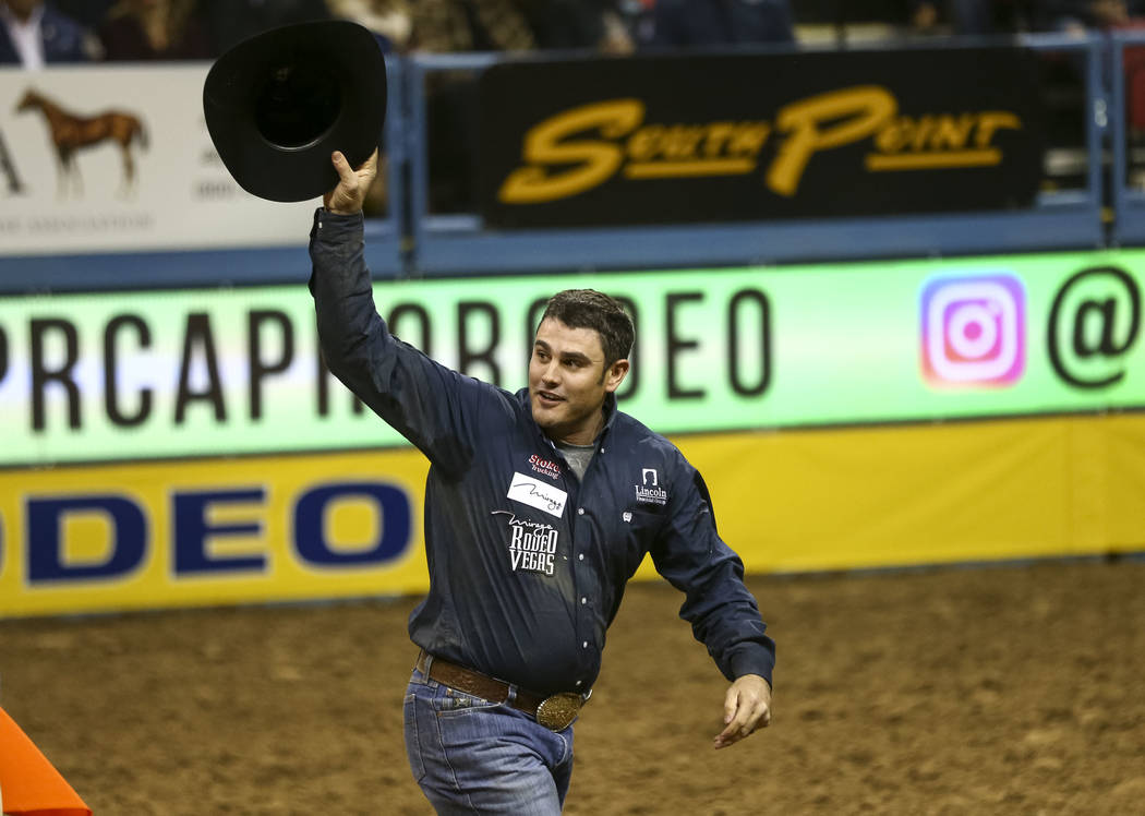 Baylor Roche of Tremonton, Utah takes waves at the crowd after taking part in the steer wrestling competition in the sixth go-round of the Wrangler National Finals Rodeo, Tuesday, Dec. 12, 2017, a ...