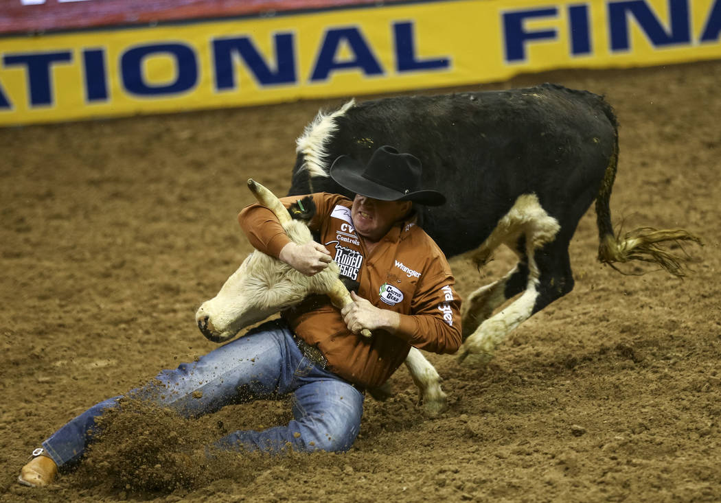 Tanner Milan of Cochrane, Alberta takes part in the steer wrestling competition in the sixth go-round of the Wrangler National Finals Rodeo, Tuesday, Dec. 12, 2017, at the Thomas & Mack Center ...