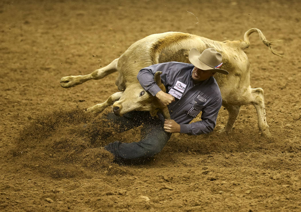 Olin Hannum of Malad, Idaho takes part in the steer wrestling competition in the sixth go-round of the Wrangler National Finals Rodeo, Tuesday, Dec. 12, 2017, at the Thomas & Mack Center in La ...