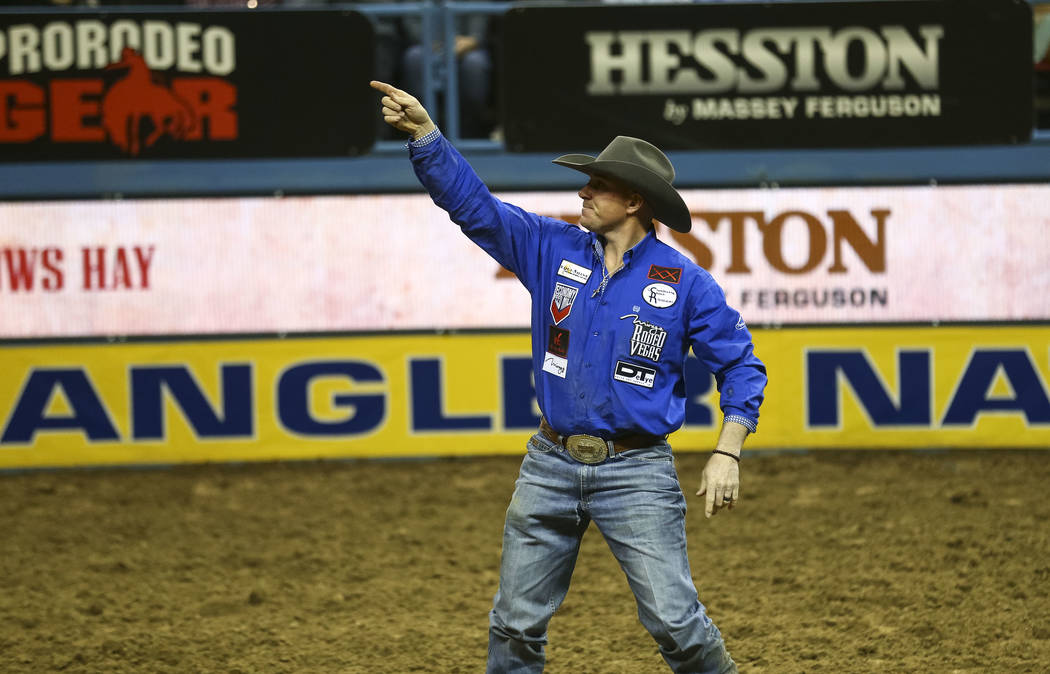 Jon Ragatz of Beetown, Wisconsin points at the crowd after taking part in the steer wrestling competition in the sixth go-round of the Wrangler National Finals Rodeo, Tuesday, Dec. 12, 2017, at th ...