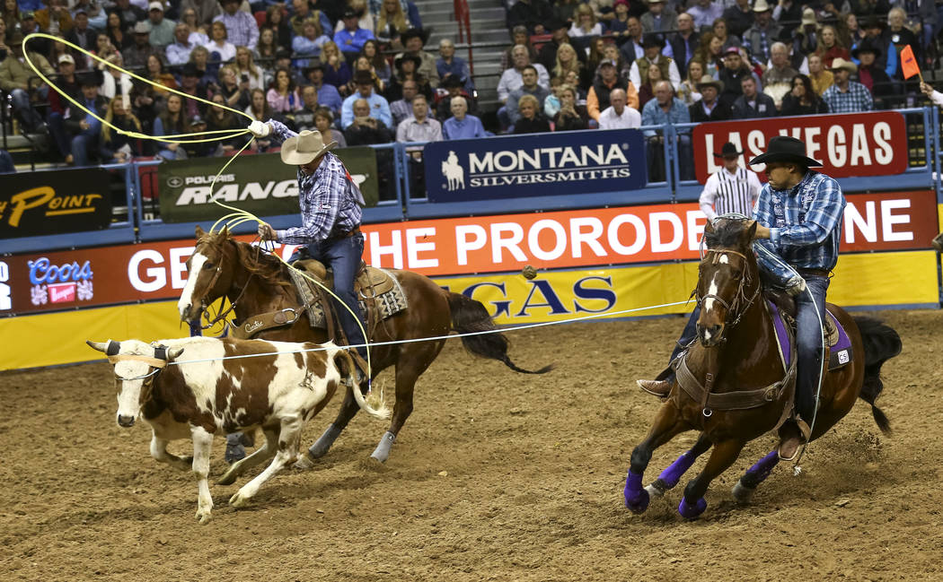 Cory Petska, left, and Erich Rogers take part in the team roping competition in the sixth go-round of the Wrangler National Finals Rodeo, Tuesday, Dec. 12, 2017, at the Thomas & Mack Center in ...