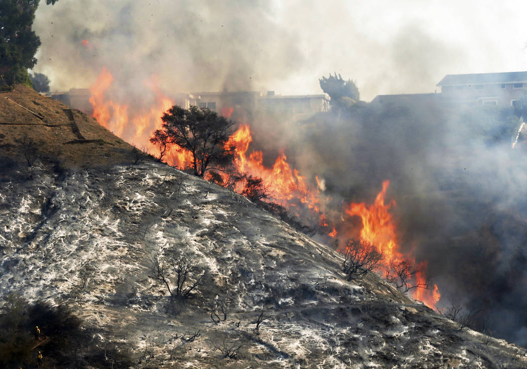 In this Wednesday, Dec. 6, 2017 file photo, flames sweep up a steep canyon wall, threatening homes on a ridge line as the Skirball wildfire swept through the Bel Air district of Los Angeles. The L ...