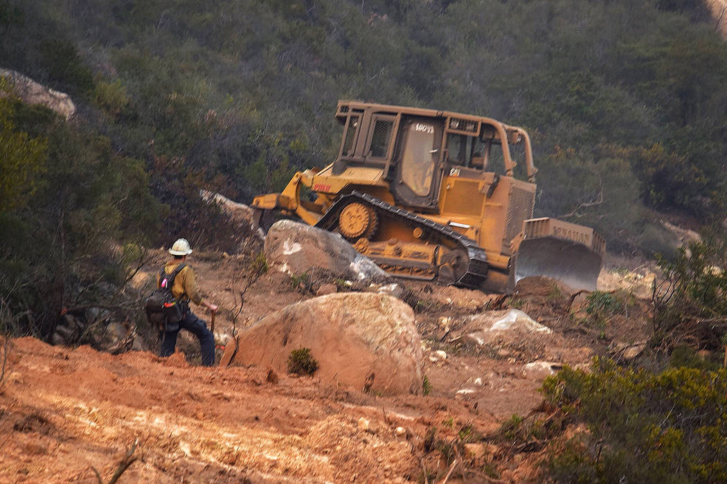 In this photo provided by the Santa Barbara County Fire Department, a member of a Santa Barbara County Fire Crew keeps an eye on a bulldozer building a fire break in the hills above Bella Vista Dr ...