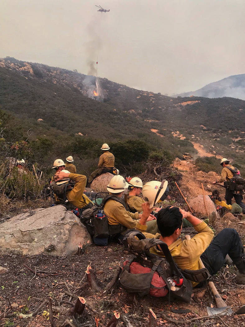 In this photo provided by the Santa Barbara County Fire Department, a Santa Barbara County Fire Crew rests after cutting a fuel break above Bella Vista Drive in Montecito, Calif., as a helicopter  ...