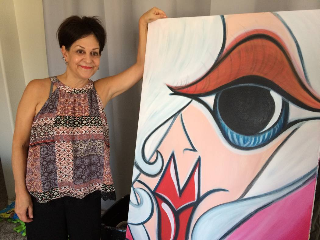 Caryn Citronpose by her painting Sept. 12, 2017, as she talks about how she turned to art to alleviate pain. She suffered a concussion which led to having a stroke. (Jan Hogan/View)