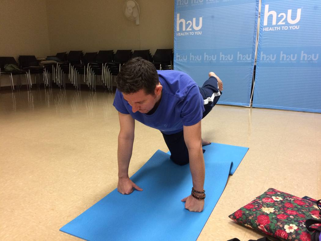 Christian Kaufman (left) leads a yoga class Nov. 30, 2017, at H2U offices, part of MountainView Hospital. It is only one of the fitness programs offered there. The class is usually held each week  ...
