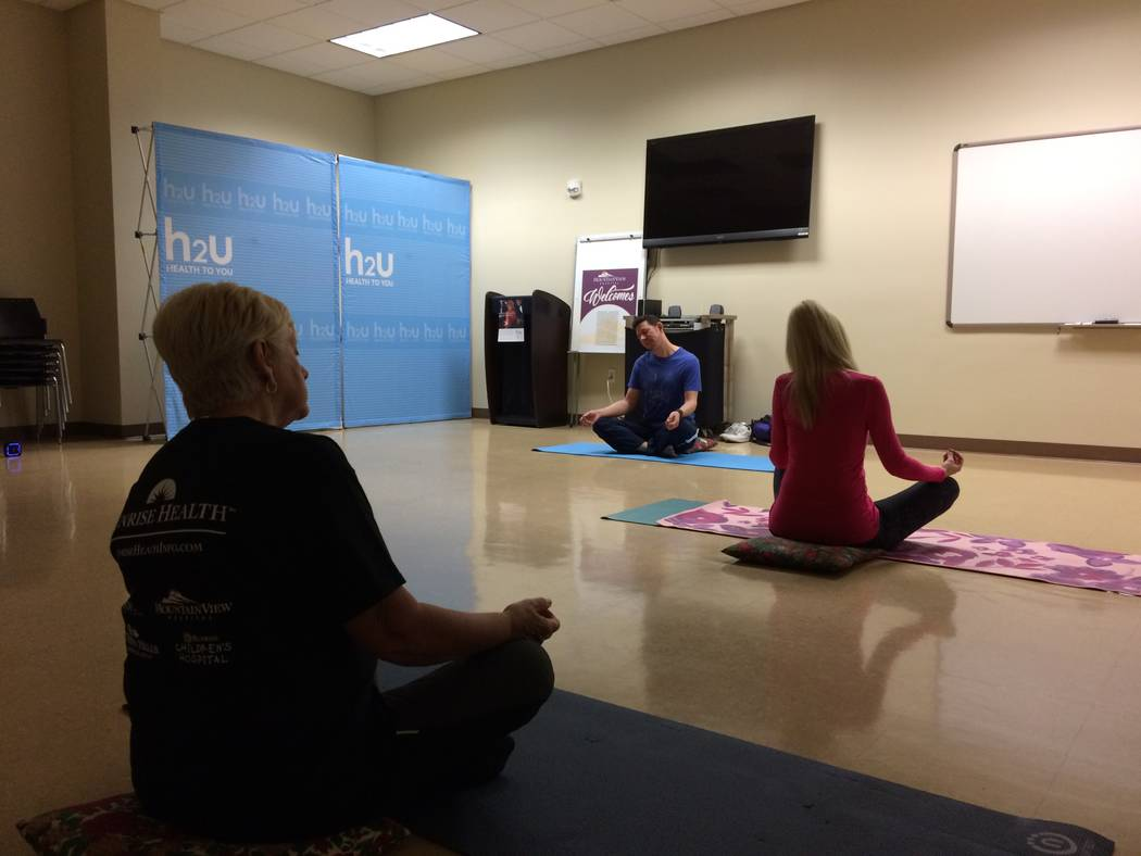 Barb Jones, new to yoga, sits in the back as Christian Kaufman leads the class Nov. 30, 2017, at H2U offices, part of MountainView Hospital. The H2U programs help its members with a variety of pro ...