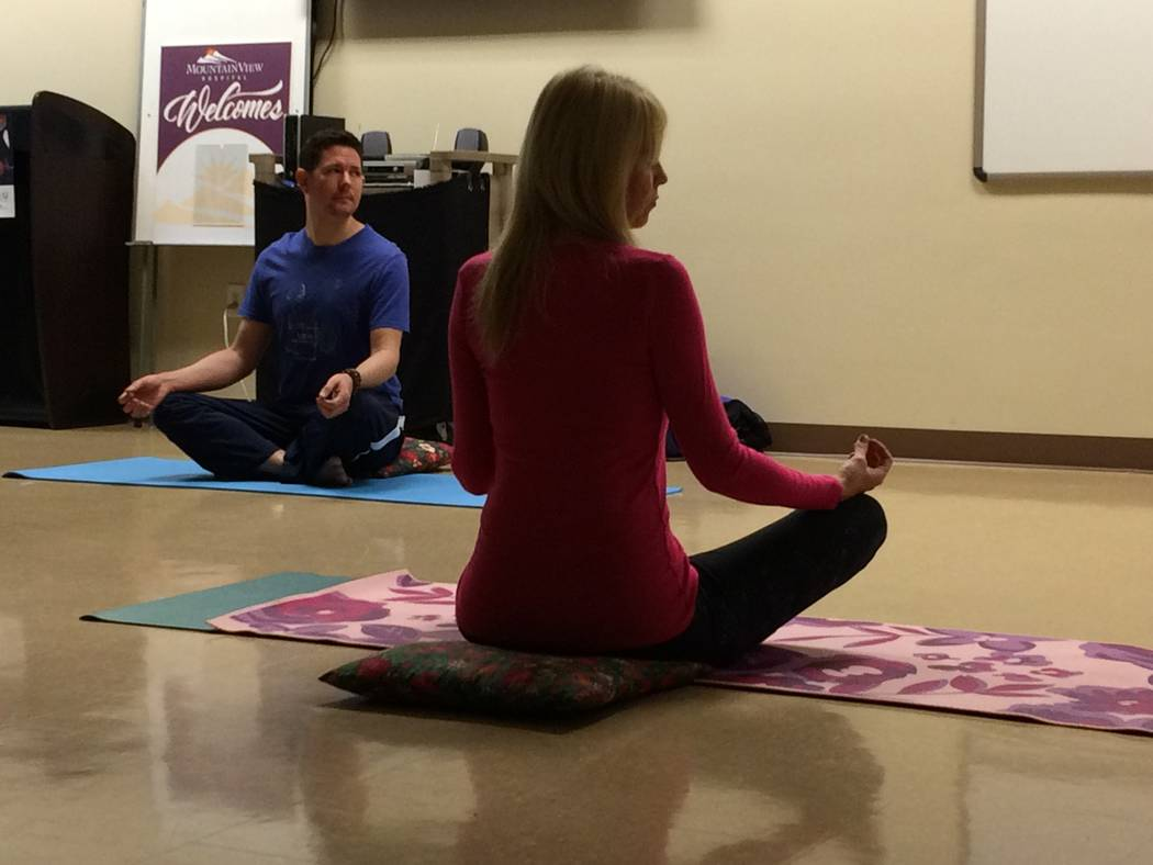 Christian Kaufman (left) leads a yoga class Nov. 30, 2017, at H2U offices, part of MountainView Hospital. Kerry Fezza, who has been practicing yoga for 10 years is seen in the foreground in the lo ...
