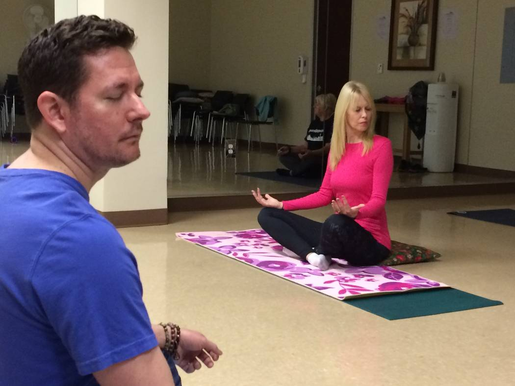 Christian Kaufman (left) leads a yoga class Nov. 30, 2017, at H2U offices, part of MountainView Hospital. Kerry Fezza, who has been practicing yoga for 10 years follows his lead in neck stretches  ...