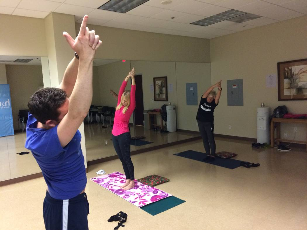 Christian Kaufman (left) leans right as he leads a yoga class Nov. 30, 2017, at H2U offices, part of MountainView Hospital. It is only one of the fitness programs offered there. (Jan Hogan/View)