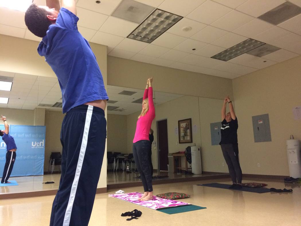 Christian Kaufman (left) reaches for the sky as he leads a yoga class Nov. 30, 2017, at H2U offices, part of MountainView Hospital. It is only one of the fitness programs offered there. (Jan Hogan ...