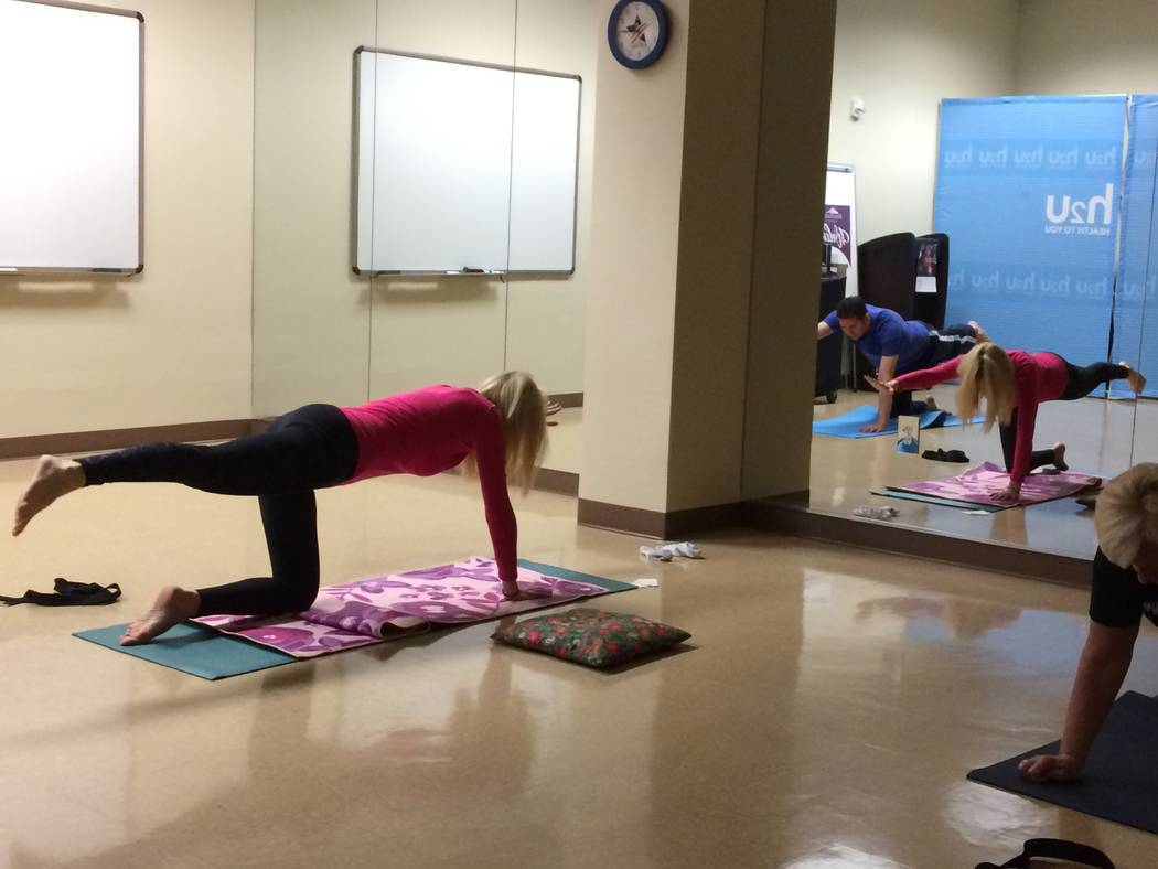 """Kerry Fezza practices yoga Nov. 30, 2017, at H2U offices, part of MountainView Hospital. Christian Kaufman leads the class. The class ends with a 20-minute meditation period. """"Yoga wasn't crea ..."""