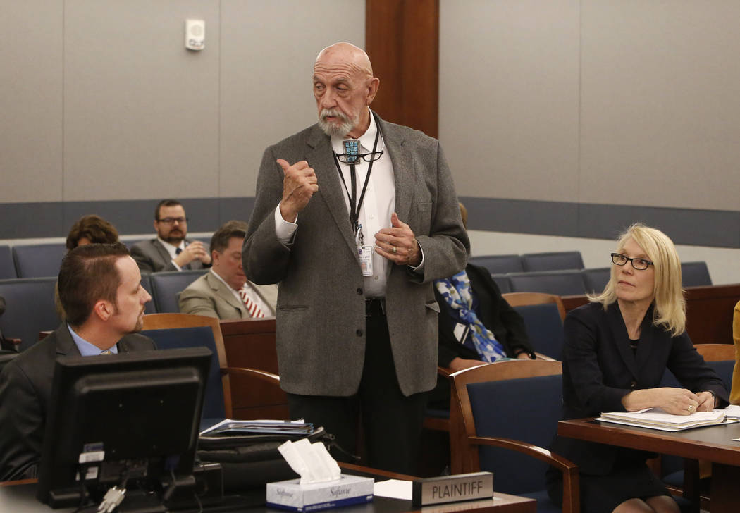 Clark County Public Administrator John Cahill, center, speaks as Samuel Warren, left, representing Travis Phippen, whose father died in his arms during the Oct. 1 shooting, and attorney Alice Dent ...