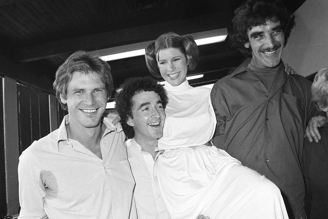 "Actor Harrison Ford, left, who played Han Solo in the move ""Star Wars,"" is pictured with his co-stars, Anthony Daniels, who played C-3P0; Carrie Fisher who played Princess Leia,  ..."