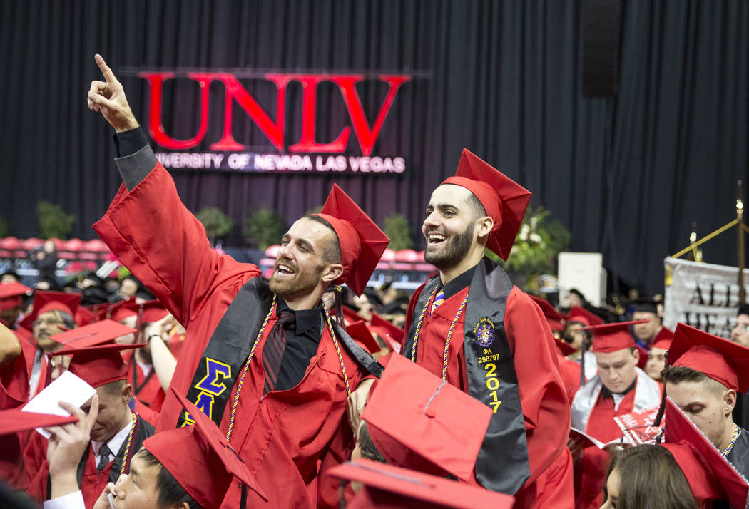 University of Nevada Las Vegas students Trent Beers, left, and Jordan Levy stand on their seats before the start of UNLV's 54th commencement ceremony at the Thomas & Mack Center on Tuesday, De ...