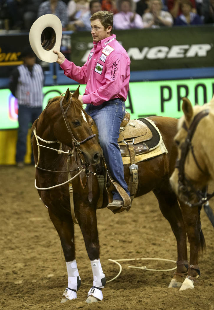 Tyson Durfey of Weatherford, Texas waves his hat at the crowd after taking part in the tie-down roping competition during the seventh go-round of the National Finals Rodeo, Wednesday, Dec. 13, 201 ...