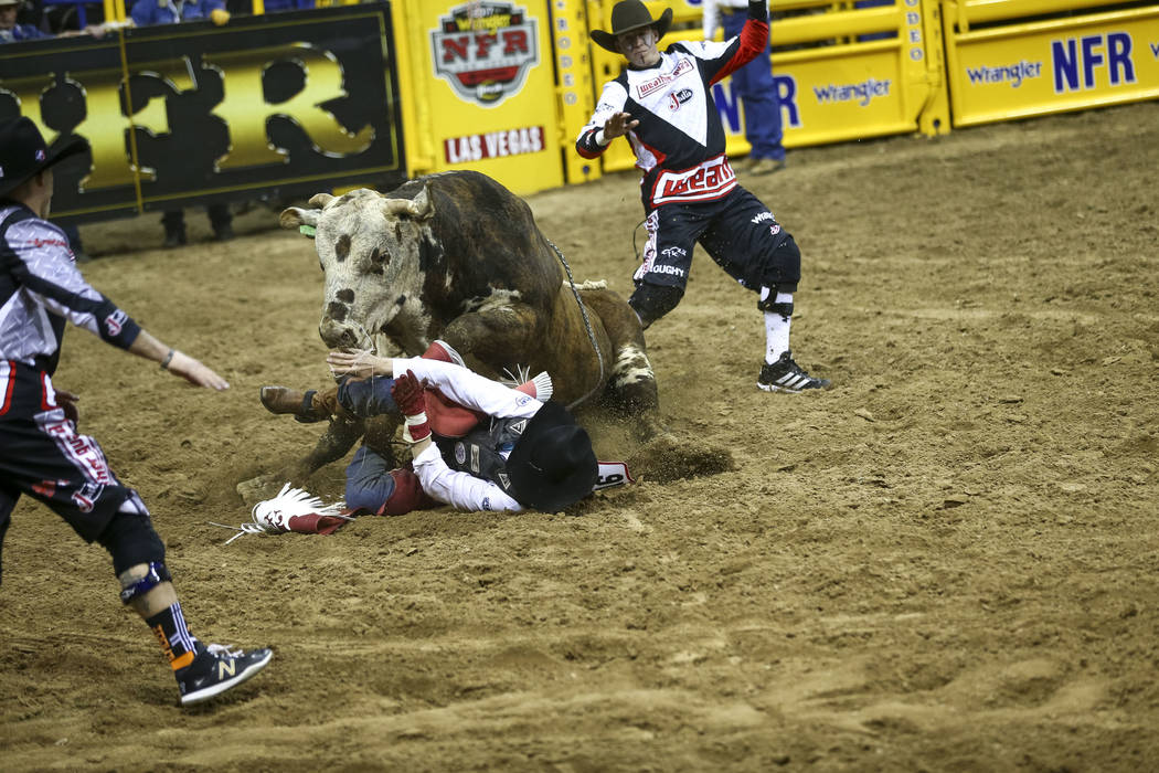 Guthrie Murray of Miami, Oklahoma is charged by Muley Maddness in the bull riding competition during the seventh go-round of the National Finals Rodeo, Wednesday, Dec. 13, 2017, at the Thomas &amp ...