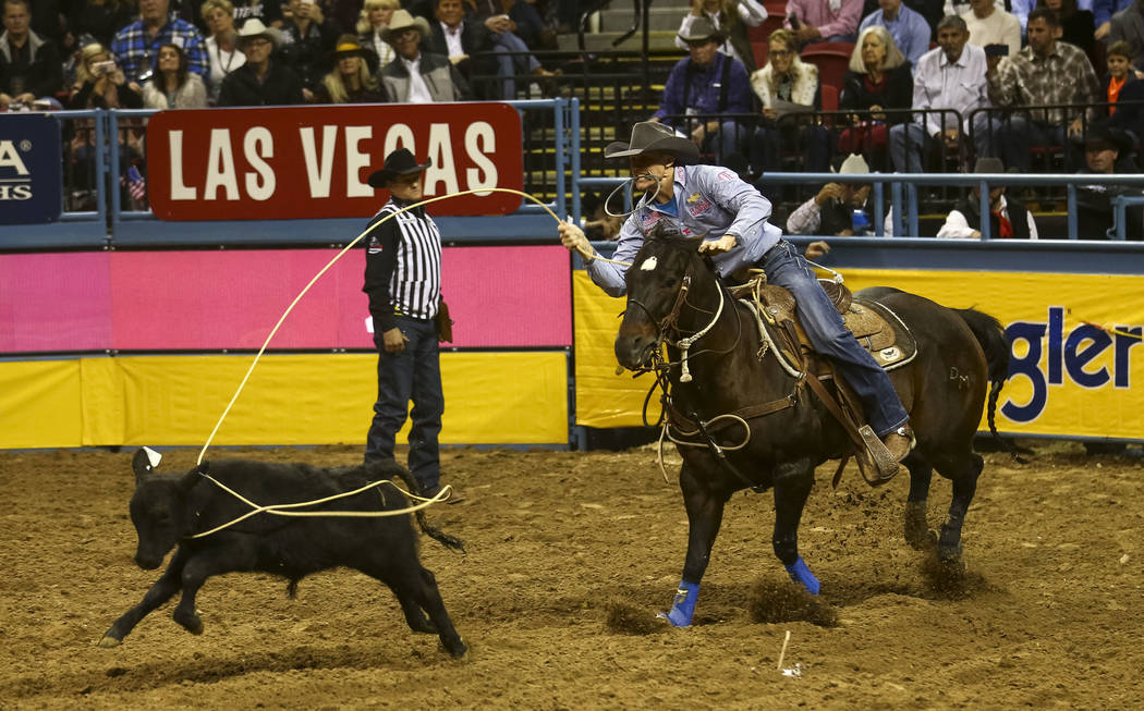 Tuf Cooper of Weatherford, Texas takes part in the tie-down roping competition during the seventh go-round of the National Finals Rodeo, Wednesday, Dec. 13, 2017, at the Thomas & Mack Center i ...