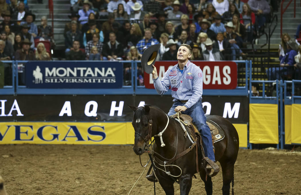 Tuf Cooper of Weatherford, Texas waves at the crowd after taking part in the tie-down roping competition during the seventh go-round of the National Finals Rodeo, Wednesday, Dec. 13, 2017, at the  ...