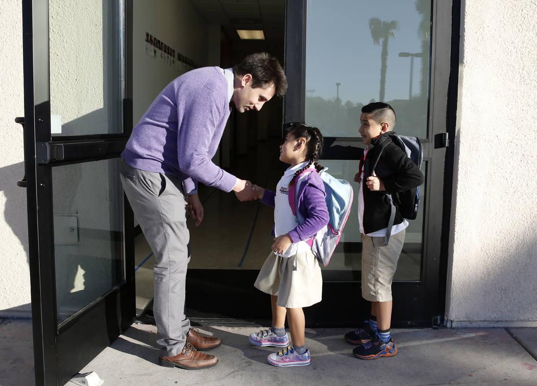 Mia Venegas, 6, and her brother Andres, 7, greeted by Ignacio Prado, Futuro Academy executive director, as they arrive to the academy, Thursday, Nov. 9, 2017, in Las Vegas. Bizuayehu Tesfaye/Las V ...