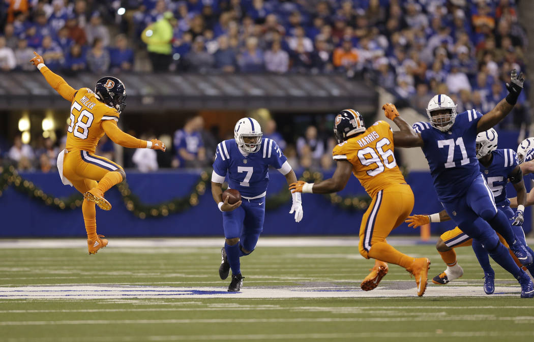 Indianapolis Colts quarterback Jacoby Brissett (7) avoids Denver Broncos outside linebacker Von Miller (58) during the first half of an NFL football game in Indianapolis, Thursday, Dec. 14, 2017.  ...