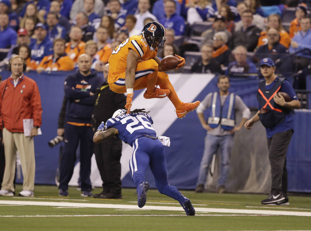 Denver Broncos running back Devontae Booker (23) leaps over Indianapolis Colts free safety Clayton Geathers (26) during the first half of an NFL football game in Indianapolis, Thursday, Dec. 14, 2 ...
