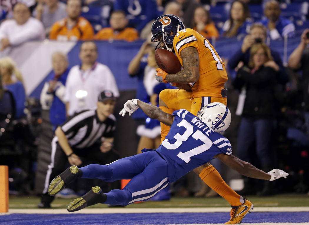 Denver Broncos wide receiver Cody Latimer (14) makes a catch for a touchdown over Indianapolis Colts cornerback D.J. White (37) during the second half of an NFL football game in Indianapolis, Thur ...