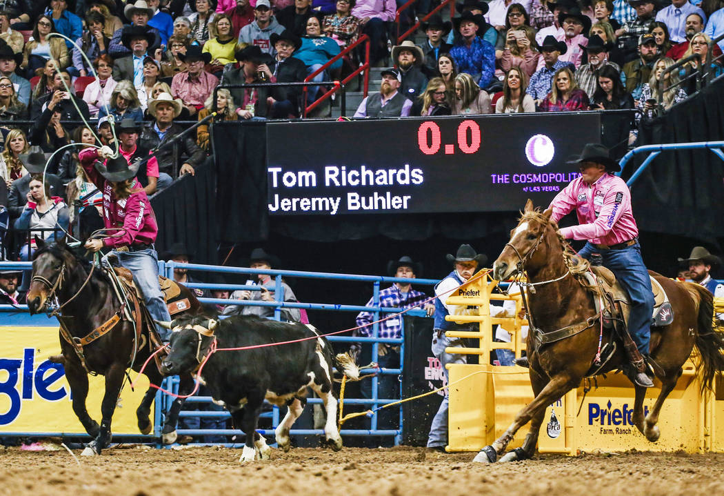 Jeremy Buhler of Arrowwood, Alberta, left, and Tom Richards of Humboldt, Ariz., work on a 4.0-second effort in team roping Tuesday night in the Wrangler National Finals Rodeo at the Thomas & M ...