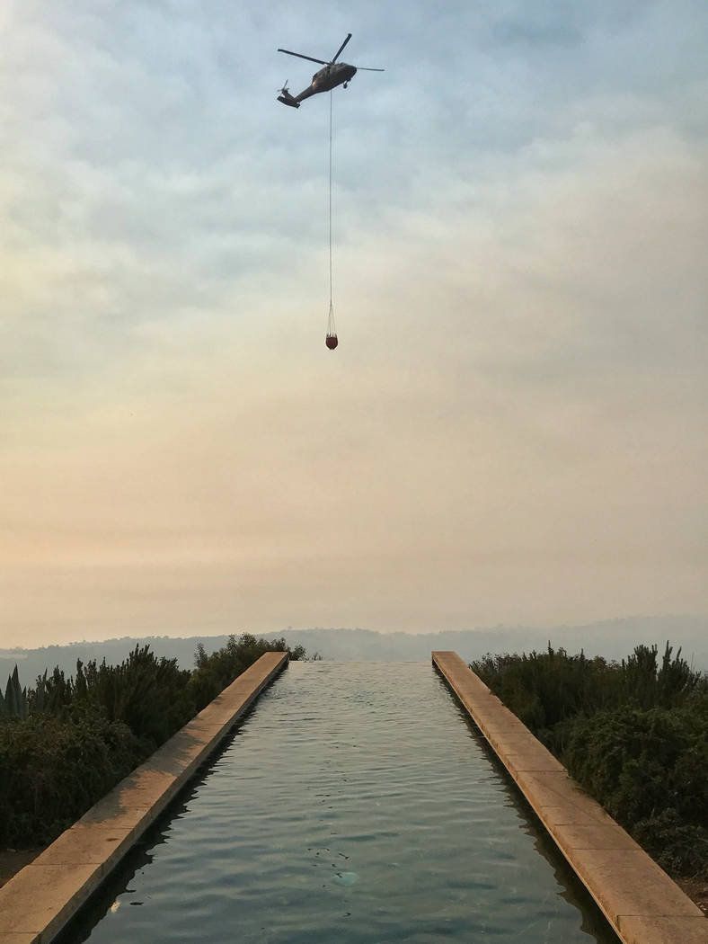 In this photo provided by the Santa Barbara County Fire Department, a helicopter making a water drop run flies over an infinity pool behind a home off Bella Vista Dr. in Montecito, Calif., Wednesd ...