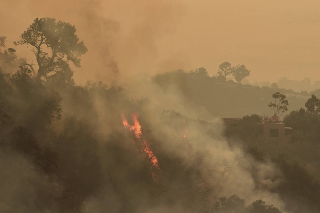 Pockets of unburned vegetation flare up off Bella Vista Dr. in Montecito, Calif., Wednesday, Dec. 13, 2017. After announcing increased containment on the Thomas fire, one of the biggest wildfires  ...