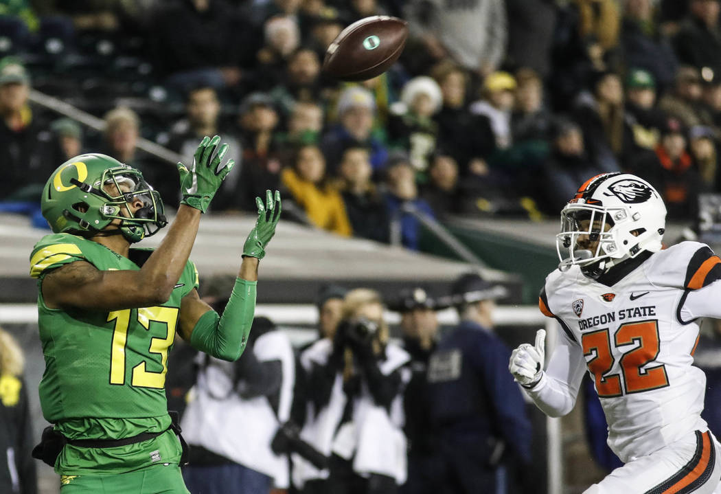 Oregon wide receiver Dillon Mitchell (13), catches a first half touchdown pass against Oregon State cornerback Isaiah Dunn (22), in an NCAA college football game Saturday, Nov. 25, 2017 in Eugene, ...