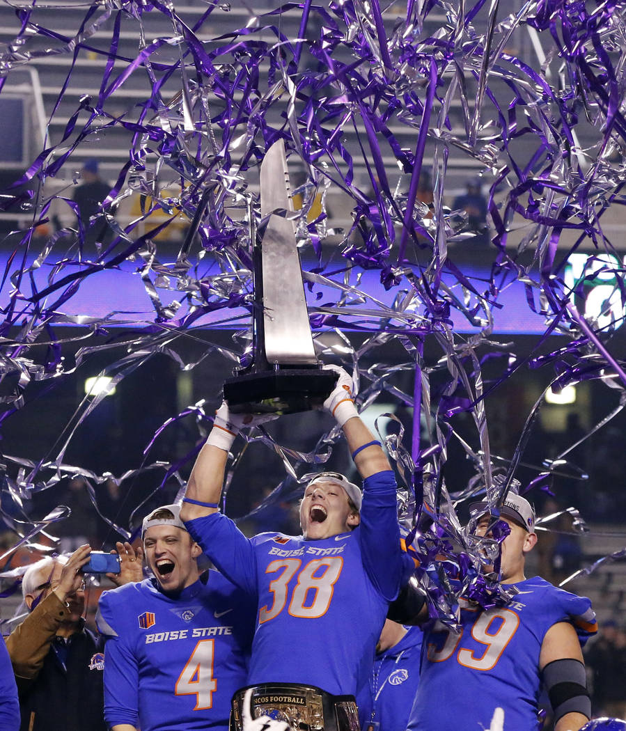 Boise State linebacker Leighton Vander Esch (38), with quarterback Brett Rypien (4) and offensive linesman Mason Hampton (59), holds up the trophy after the team's 17-14 win over Fresno State in a ...