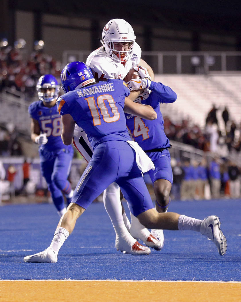 Boise State safety Kekoa Nawahine (10) and cornerback Tyler Horton pick up Fresno State tight end Jared Rice as they tackle him short of the goal line during the first half of an NCAA college foot ...